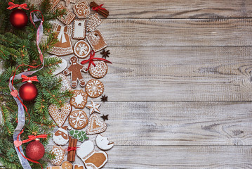 Christmas background with copy space. Traditional gingerbread, christmas tree branch,  Christmas spices and red Christmas decor on old white wooden background.
