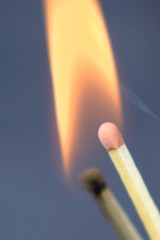 Matches are burning against a dark background