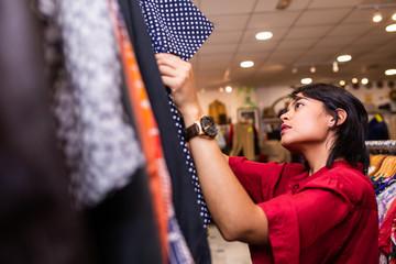 Cheerful woman choosing clothing in shop