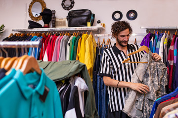 Cheerful man choosing clothing and accessories in shop