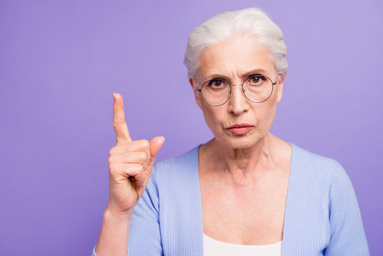 Portrait of grey haired old strict woman wearing glasses pointin