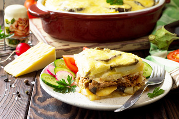 Eggplant casserole with beshamel (moussaka) - a traditional Greek dish on the kitchen wooden background. Copy space.