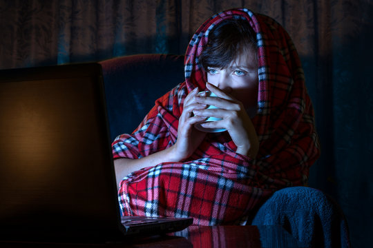A young girl wrapped in a blanket spends an evening watching a movie on a laptop