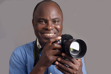 close-up of an adult african man and camera, smiling.