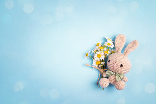 Cute toy bunny with chamomile flowers and copy space on a blue background.