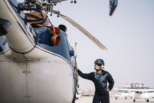 Pilot girl poses with her helicopter.