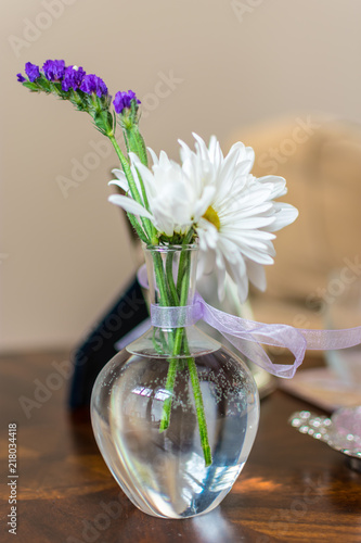 Purple And White Flowers In Glass Vase Filled With Water And Tied
