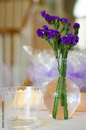 Purple Flowers In Vase Next To Empty Plastic Cup In Indoor Bright