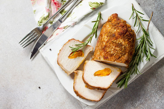 Meat roll (roulade) with with apricot stuffing and spices on a light stone or slate background. Thanksgiving day appetizer. Top view flat lay background, copy space.