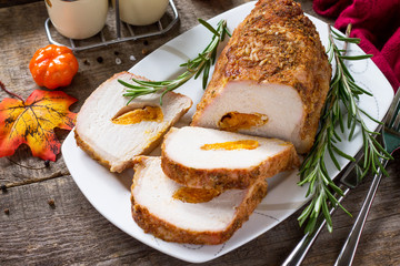 Meat roll (roulade) with with apricot stuffing and spices on a kitchen wooden table. Thanksgiving day appetizer.