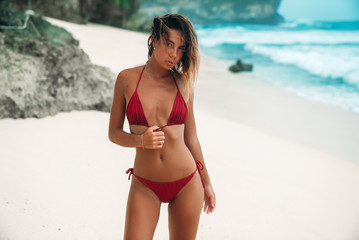 A sexy model in a red swimsuit walks along a deserted white sandy beach. The wind blows her curly hair.