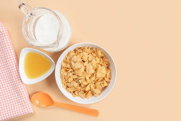 corn flakes in a bowl with jug of milk honey napkin and plastic spoon on orange background, copy space for text. quick breakfast for modern lifestyle concept.