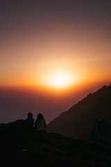 A couple who watching sunset on the mountain