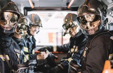 unrecognizable firemen with helmet in an emergency vehicle