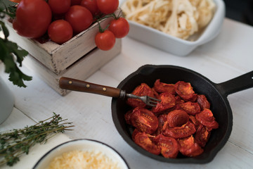 Italian food cooking ingredients on white table with sun-dried tomatoes, herbs and garlic, fresh vegetables, pasta, cheese parmesan and spices. Balanced nutrition. Cooking, culinary, food concept.