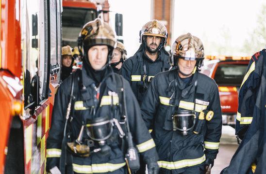 Firemen walking at fire station.