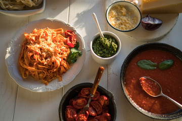Products for cooking. Tomato sauce, pasta, tomatoes, garlic, olive oil on the old wooden background. Plate of pasta with tomato sauce with ingredients for cooking on white background, top view.