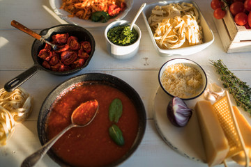 Pasta with spicy tomato sauce, parmesan and basil. Plate with delicious pasta, cheese, pan with organic tomato sauce and kitchen board on wooden table, top view. Products for cooking. Soft focus.