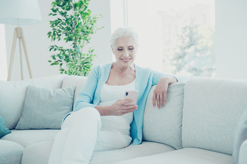 Gray-haired beautiful stylish old lady sitting on sofa, surfing