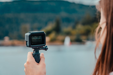 Young european woman filming with action camera lake and forest in the black forest