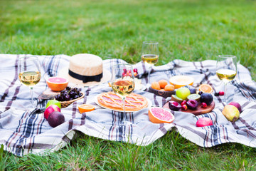 Tuinposter Picknick Picnic background with white wine and summer fruits on green grass, summertime party