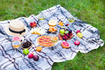 Picnic background with white wine and summer fruits on green grass, top view