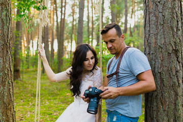 Photographer and bride watching recently taken photos