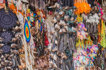 Dream catcher. Boho chic, ethnic amulet, symbol.  Amulet of native american indian. Colorful souvenir. Fluffy variety of dream catchers on artisan market. Selective focus and blurred background..