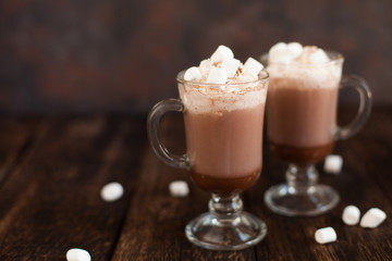 Two glasses with Hot chocolate garnished with whipped cream, marsmallow and cocoa powder.