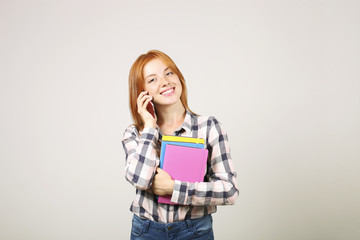 Young beautiful woman with long natural red head wearing checkered flannel shirt holding bunch of notebooks, talking on phone. Female student with smartphone & books. Background, copy space, close up.