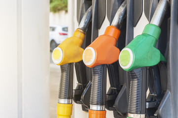 Three colored fuel pumps hooked to the gasoline dispenser