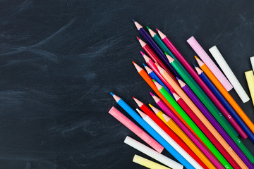 Back to School concept. Color pencils on blackboard background. Close up, flat lay, copy space, top view