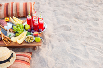 Foto auf Acrylglas Picknick Picnic on the beach at sunset in the style of boho. Concept outdoors evening healthy dinnner with fruit and juice