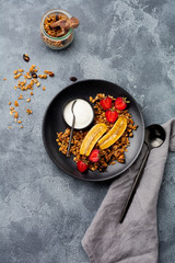 Foto op Canvas Gebakken Eieren Oatmeal granola with yoghurt, fresh strawberries and banana, chia seeds, sunflower and honey in black ceramic plate on dark background. Top view.