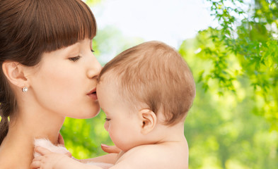 family and motherhood concept - happy smiling young mother kissing little baby over green natural background
