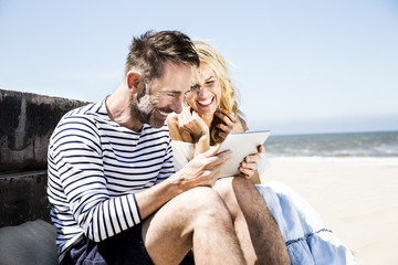 Happy couple on the beach looking at tablet