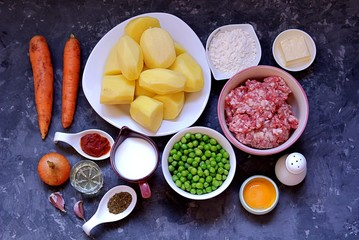 "Ingredients for a ""shepherd's pie"", the British potato casserole with minced meat and vegetables. Peeled potatoes, minced meat, butter, milk, flour, egg yolk, carrots, green peas, onion, garlic, salt"