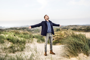 Man standing in dunes with outstretched arms
