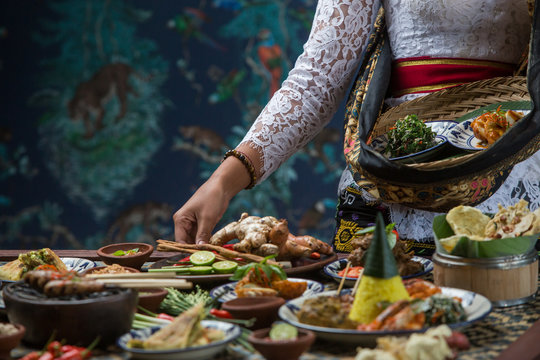 Indonesian cuisine - Many traditional Balinese dishes on the table. Waitress is serving food for some festive event, party or wedding