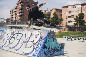 Tattooed man doing parkour in a skatepark
