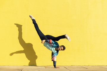 Acrobat doing movement training in front of a yellow wall