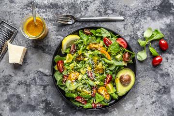 Salad with lamb's lettuce, tomatoes, avocado, parmesan and curcuma lemon dressing