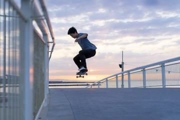 Young Chinese man skateboarding at sunsrise near the beach