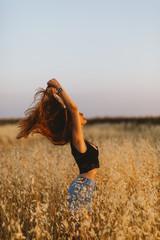 Young woman standing in grain field enjoying sunset