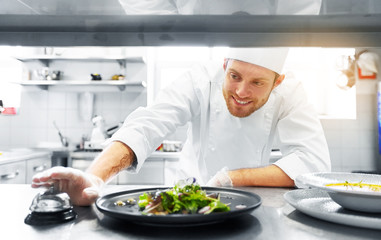 food cooking, profession and people concept - happy male chef cook with plate of soup and salad ringing bell at restaurant kitchen table