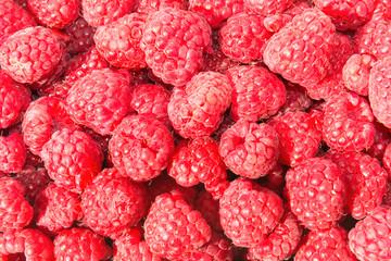 Heap of ripe juicy raspberries in wicker market box