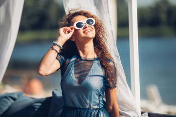 Close-up portrait of magnificent caucasian girl in round white sunglasses. Lovable long-haired brunette woman enjoying life and having fun at resort
