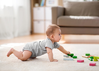 babyhood, childhood and people concept - little asian baby boy playing with toy blocks at home