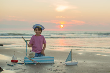 Sailor baby boy, cute child, playing on the beach with wooden boat, fishes and fishing rod on sunset