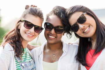female friendship, summer and eyewear - happy young women in sunglasses outdoors